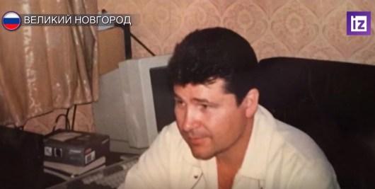 Темноволосый мужчина в белой рубашке сидит в комнате