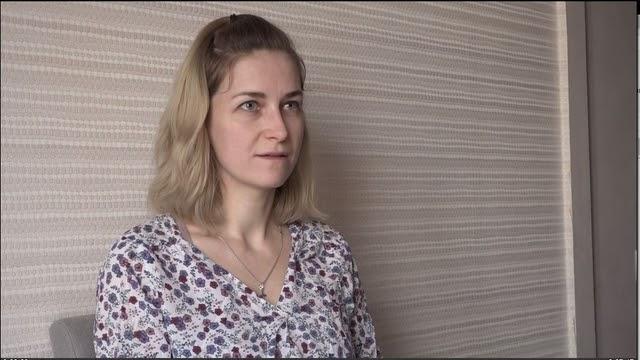 Женщина в светлой блузе сидит на фоне серой стены
