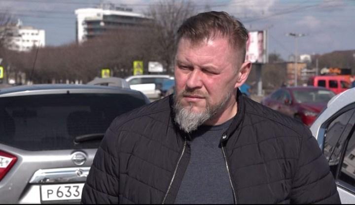 Мужчина с бородкой в черной куртке стоит на улице на фоне машины