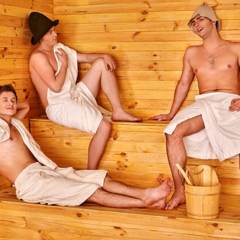 Male company in hat relaxing at sauna.