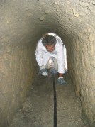 An archaeologist crawls through the ancient sewer