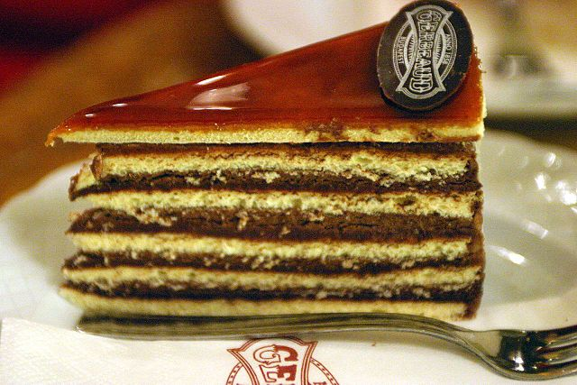 Dobos cake is a sponge cake layered with chocolate buttercream and topped with caramel. The sides are coated with ground nuts.