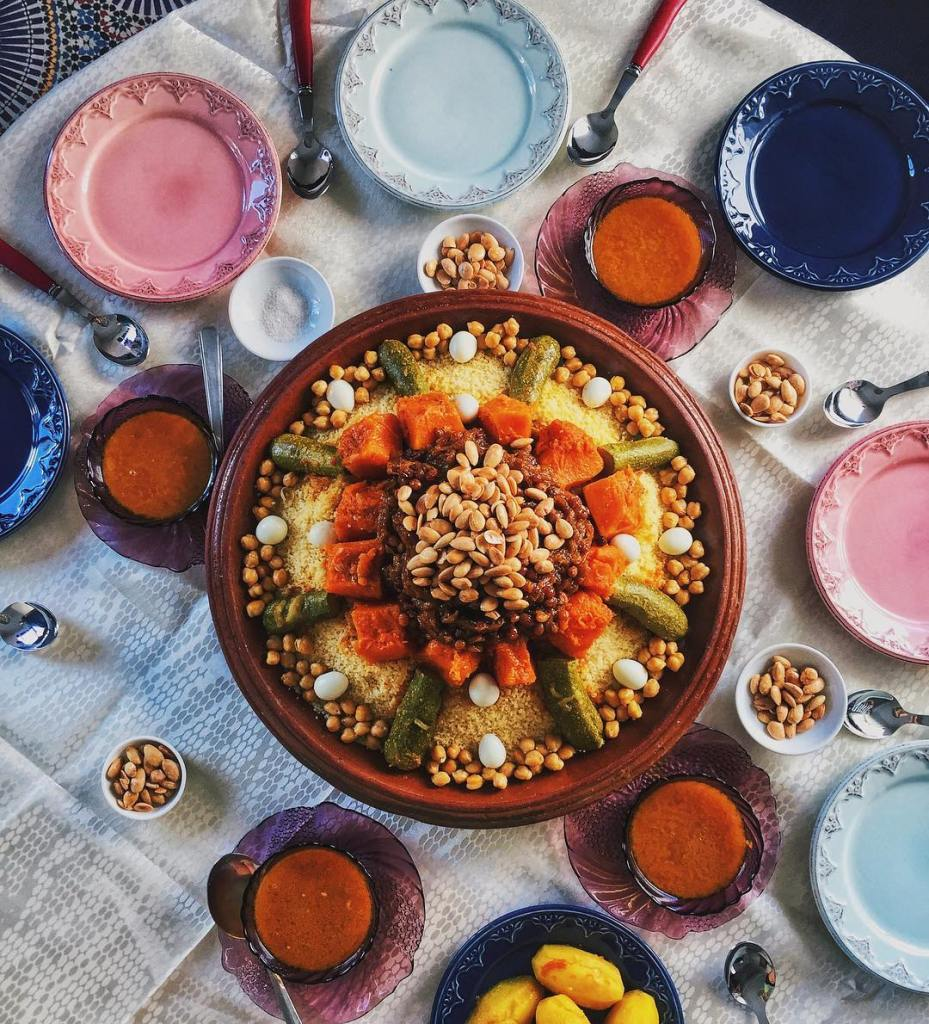 An overhead view of a communal platter of homemade Moroccan cuscus, with chunks of squash , zucchini halves, chickpeas, and partridge eggs laid on a bed of steamed cuscus, oriented around tfaya (a confection featured prominently in Moroccan cuisine made of caramelized onions with raisins, butter, and spices) topped with toasted almonds. It's surrounded by bowls of bloul, the broth collected from the pot in which the vegetables were cooked, added to taste.