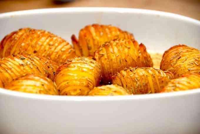 De bedste hasselbach kartofler med skræl og rosmarin. Det er nemlig ikke nødvendigt at skrælle kartoflerne, som skæres i skiver, pensles med smør, og krydres med salt og rosmarin. Mange kalder også disse kartofler for hasselbagte kartofler, men det andet er det korrekte. Foto: Guffeliguf.dk.