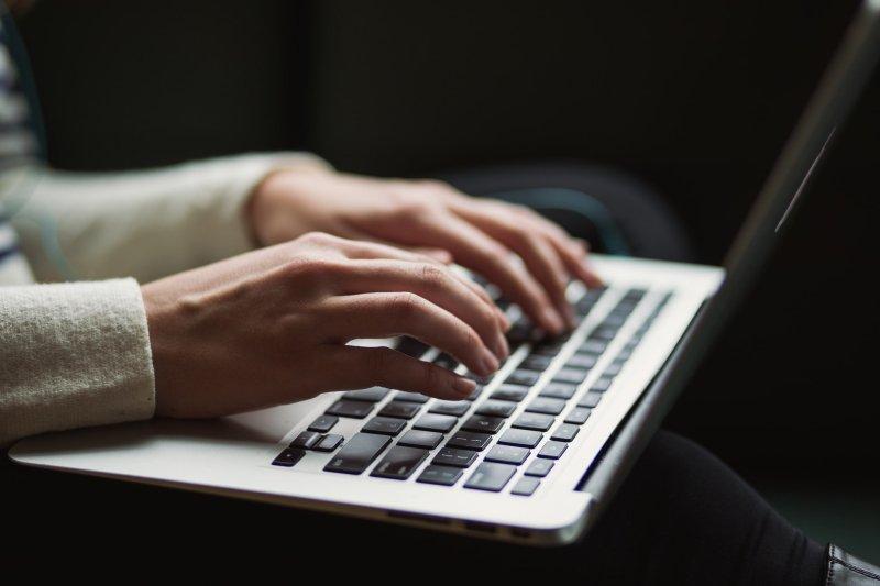 Pessoa escrevendo conteúdo usando o teclado de um notebook