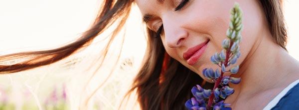 Mulher sorrindo com flores do Floral de Bach Chicory