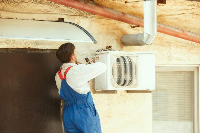 técnico instalando o ar-condicionado e tendo atenção ao fio para ar-condicionado
