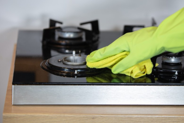 mãos de uma pessoa limpando uma trempe para indicar como desentupir fogão