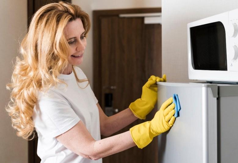 mulher mostrando como limpar geladeira