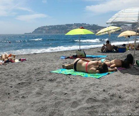 Cala Curumbico, mujeres tomando sol sobre la arena.