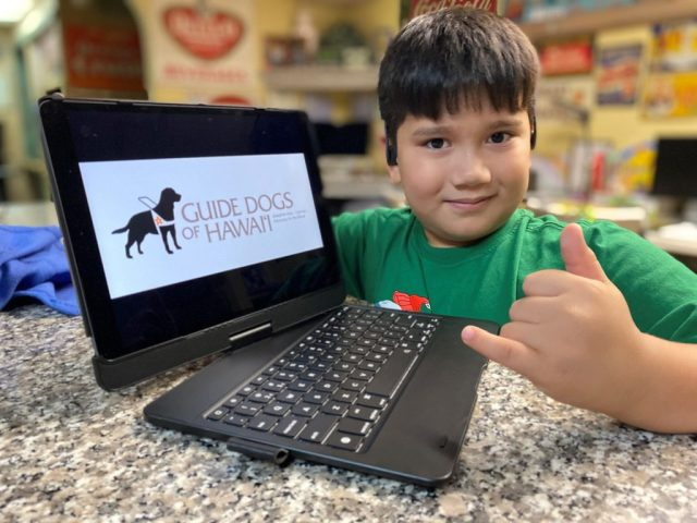 Young boy smiles and throws a shaka while showing his iPad to the camera. The iPad is in a keyboard case and displays the Guide Dogs of Hawaii logo on the screen.