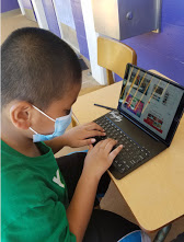 A young boy with a mask on sits at a school desk using his iPad with a keyboard case.