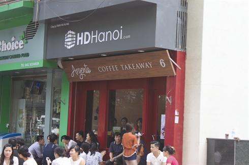 Les Vietnamiens prennent le cafe dans un Cafeterie dans les villes