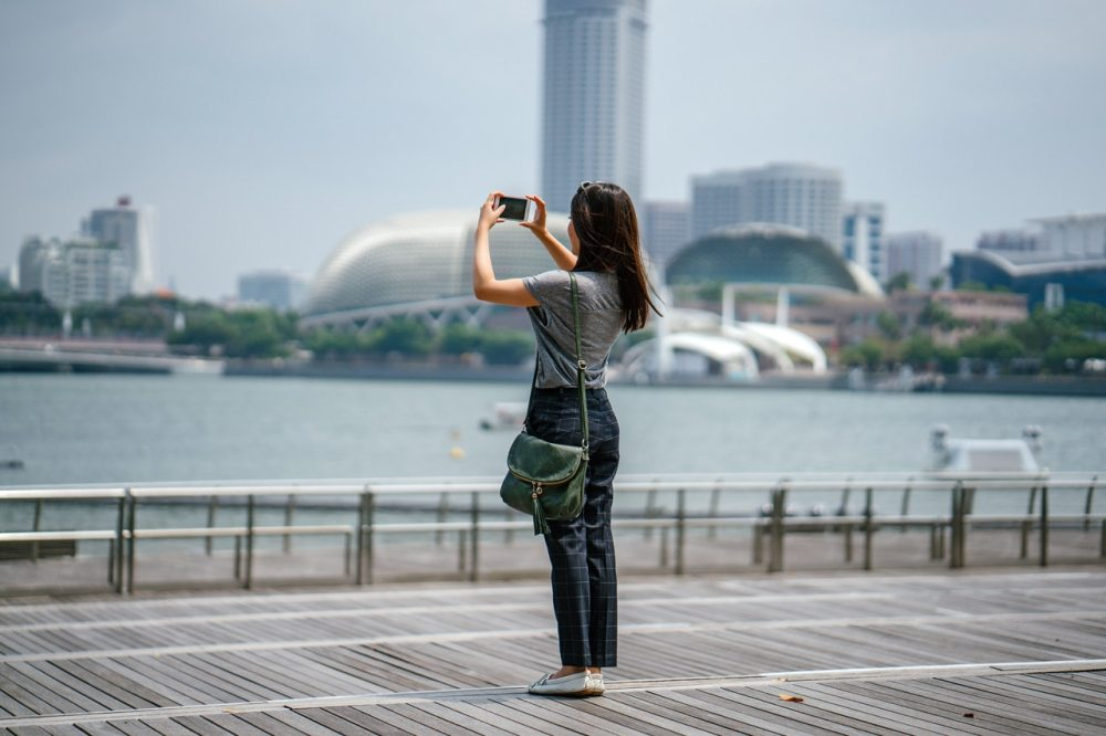 Woman Taking Photo of Scenery city