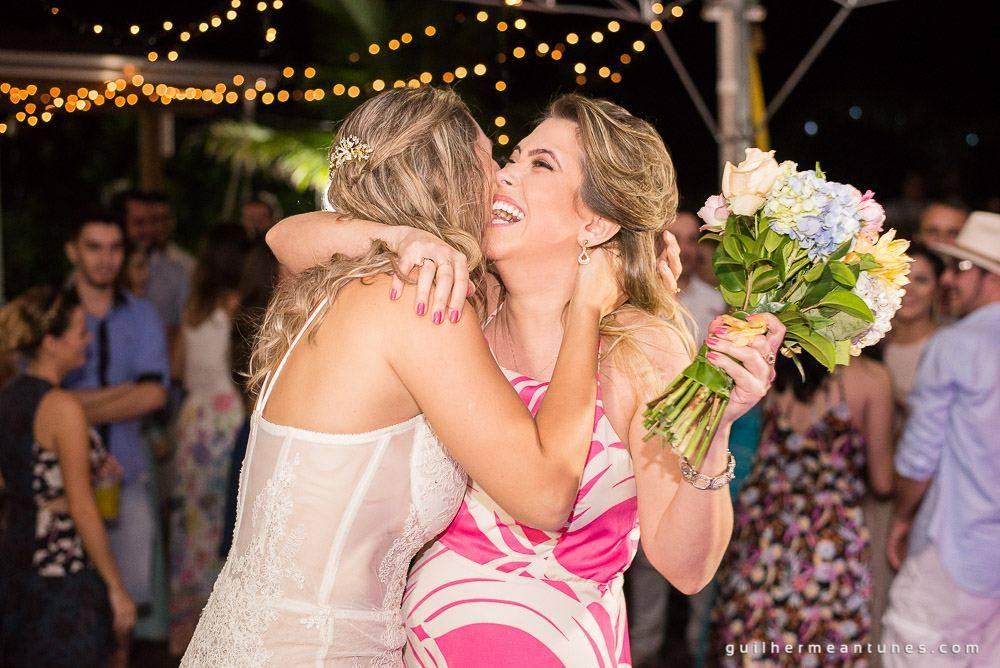 Foto de Casamento na praia de Larissa e Ronaldo abraço de noiva e convidada com buquê