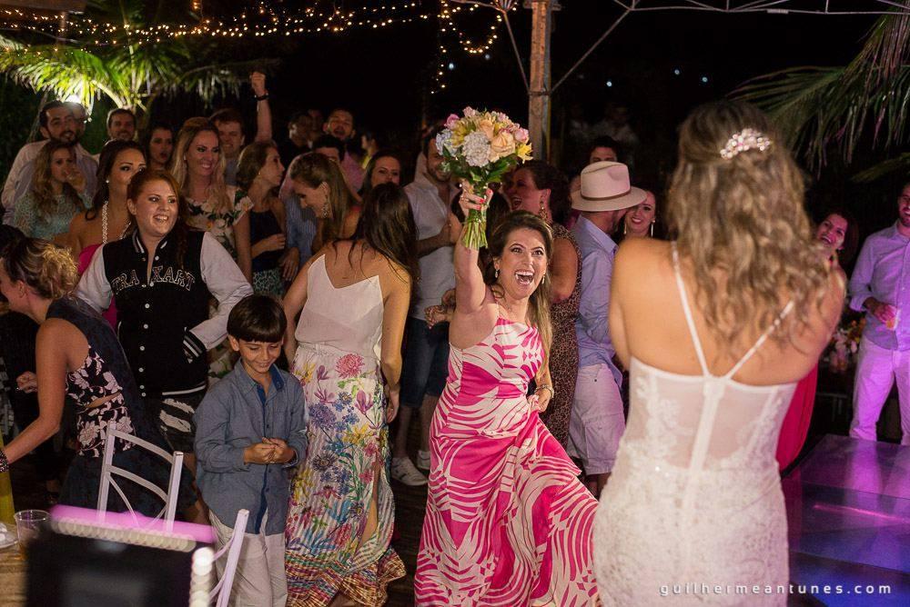 Foto de Casamento na praia de Larissa e Ronaldo convidada pega o buquê e comemora
