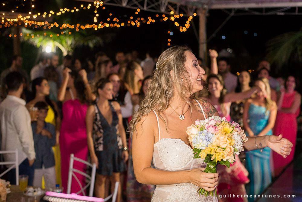 Foto de Casamento na praia de Larissa e Ronaldo noiva se prepara para jogar buquê