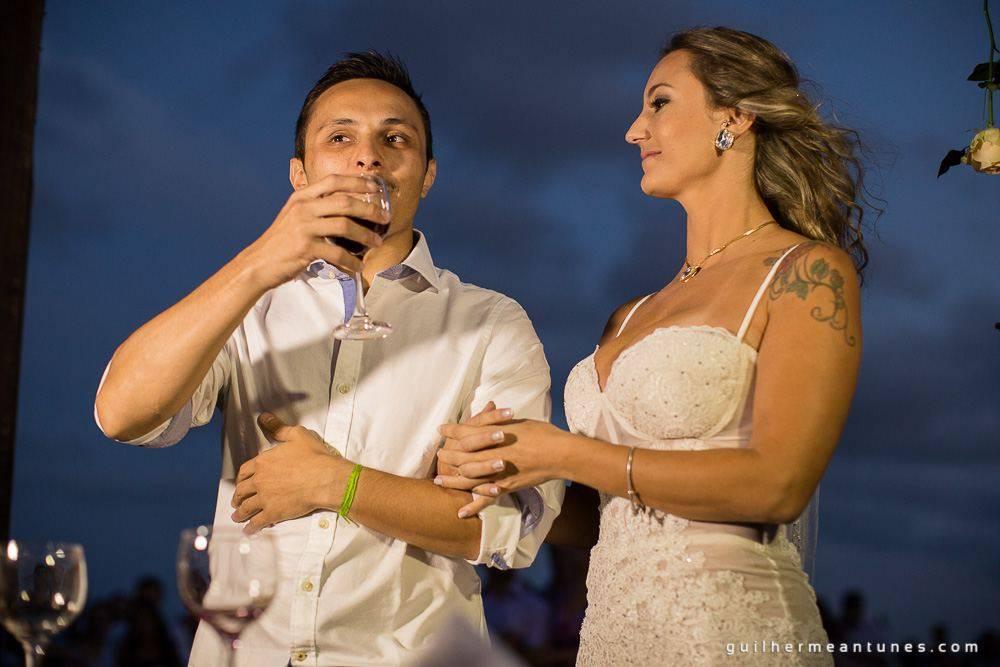 Foto de Casamento na praia de Larissa e Ronaldo noivo bebendo o brinde de tradição