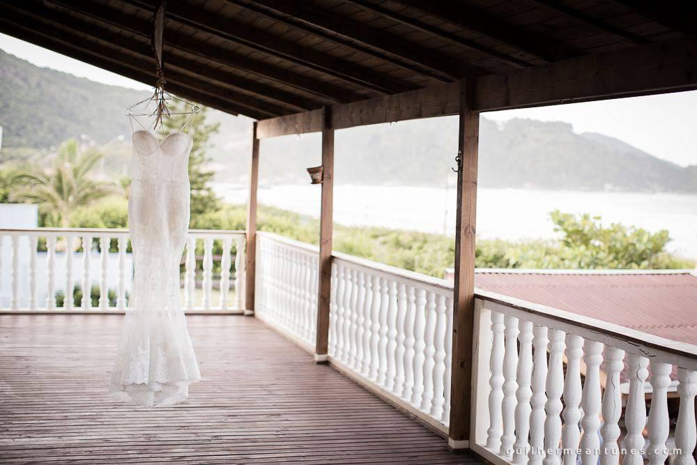 Foto de Casamento na praia de Larissa e Ronaldo vestido de noiva pendurado na varanda