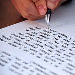 A photograph of a hand writing on lined paper
