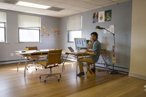"""A photograph of a young man in an open office with a hardwood floor; Published as part of the post """"UX Career Development"""""""