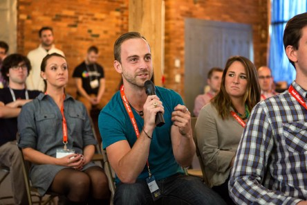 "A photo of an audience member holding a microphone, published as part of ""3 Reasons Why I Invite UX Professionals Into My Classroom"""