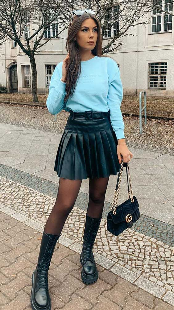 tendências de inverno, suéter azul, saia plissada, meia calça e coturno tratorado