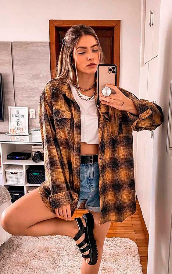 camisa oversized xadrez, t-shirt branca cropped, short jeans desfiado, papete preta