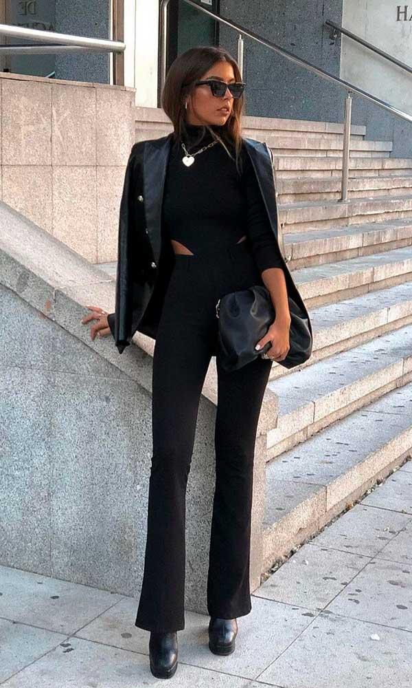 jaqueta de couro, body preto e calça flare, correntes douradas