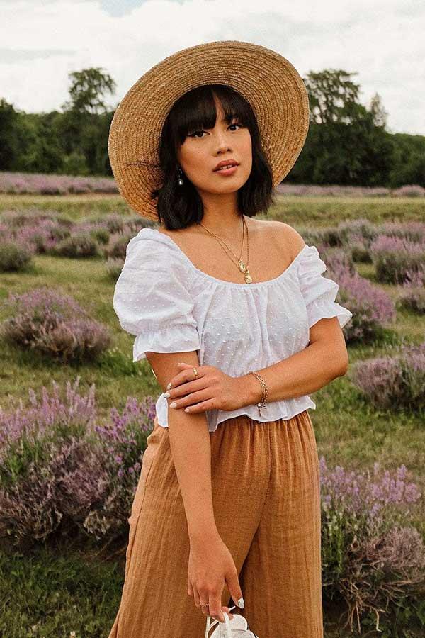 Katie Cung, chapéu de palha, batinha e calça marrom