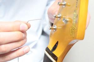 ペグ穴に弦の先端を刺し、90度に折り曲げます