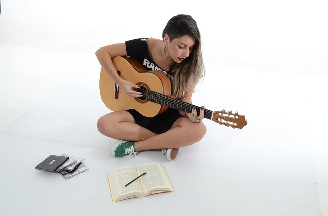 girl with guitar writing songs