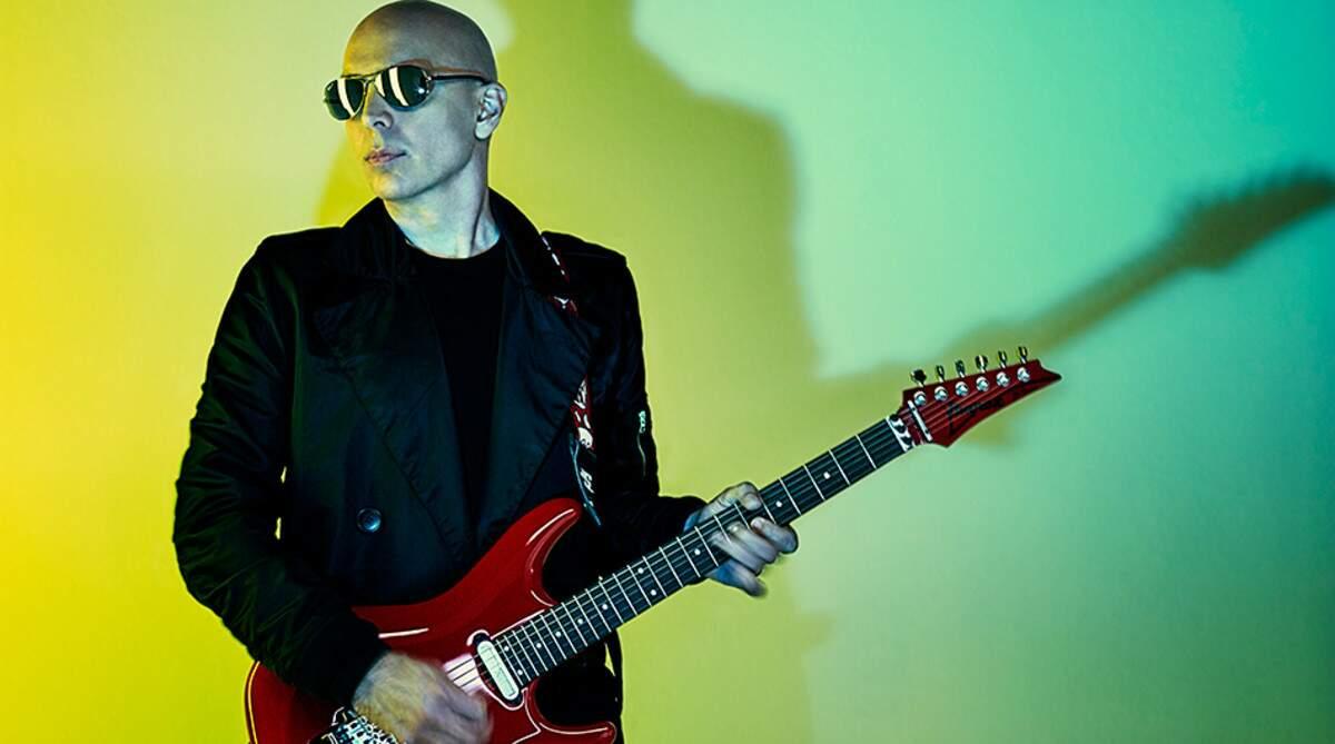 Joe Satriani tocando uma guitarra Ibanez vermelha