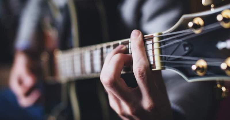 Guitarrista fazendo um acorde
