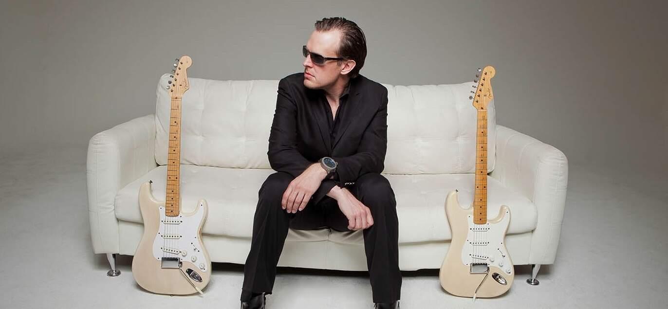 Joe Bonamassa sentado no sofá com duas guitarras Fender Stratocaster