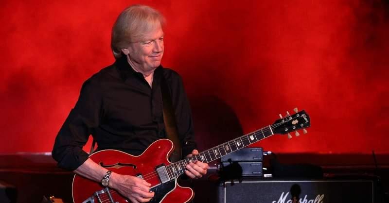 Justin Hayward tocando uma guitarra Gibson 335 vermelha