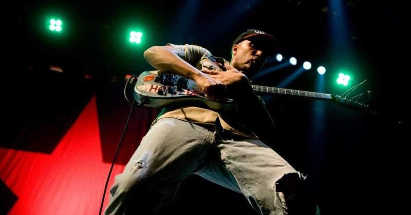 Tom Morello tocando em um palco iluminado