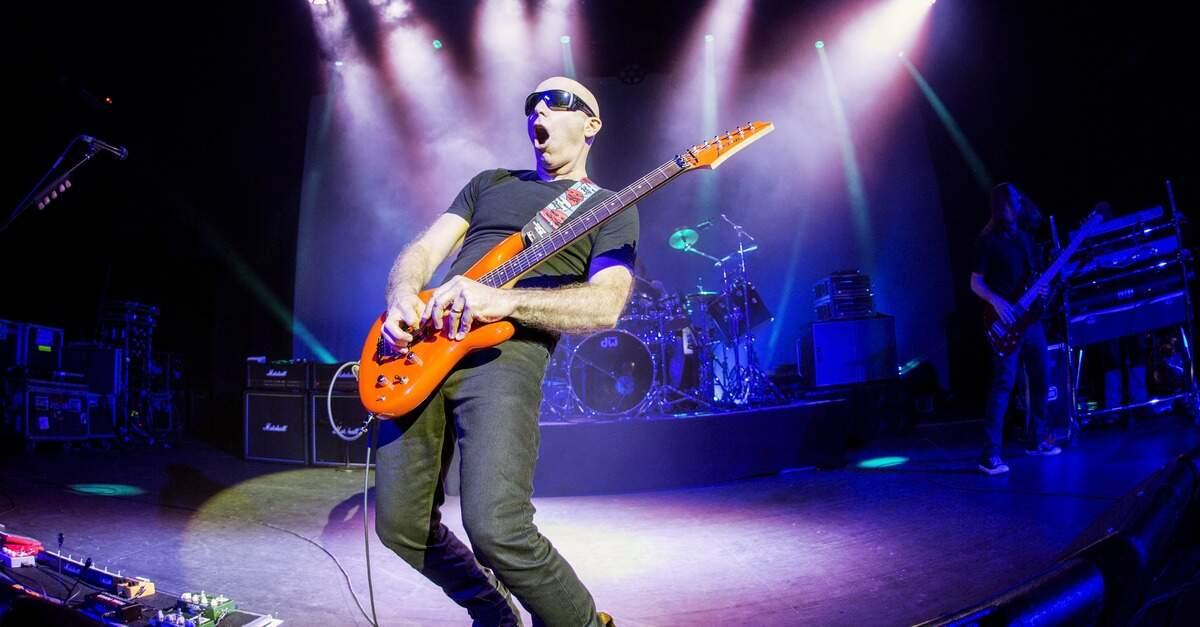 Satriani tocando uma Ibanez laranja