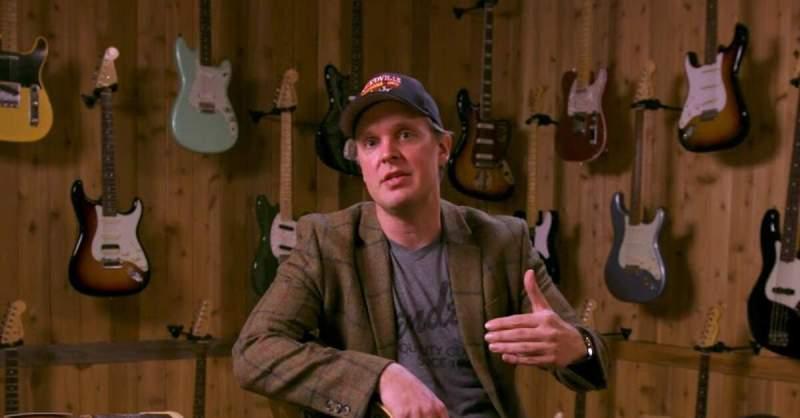 Joe Bonamassa à frente de uma parede de guitarras