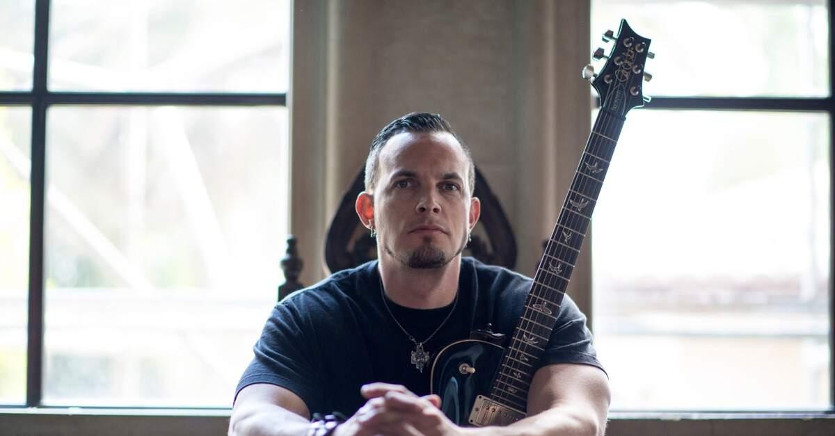 Mark Tremonti sentado com uma guitarra PRS