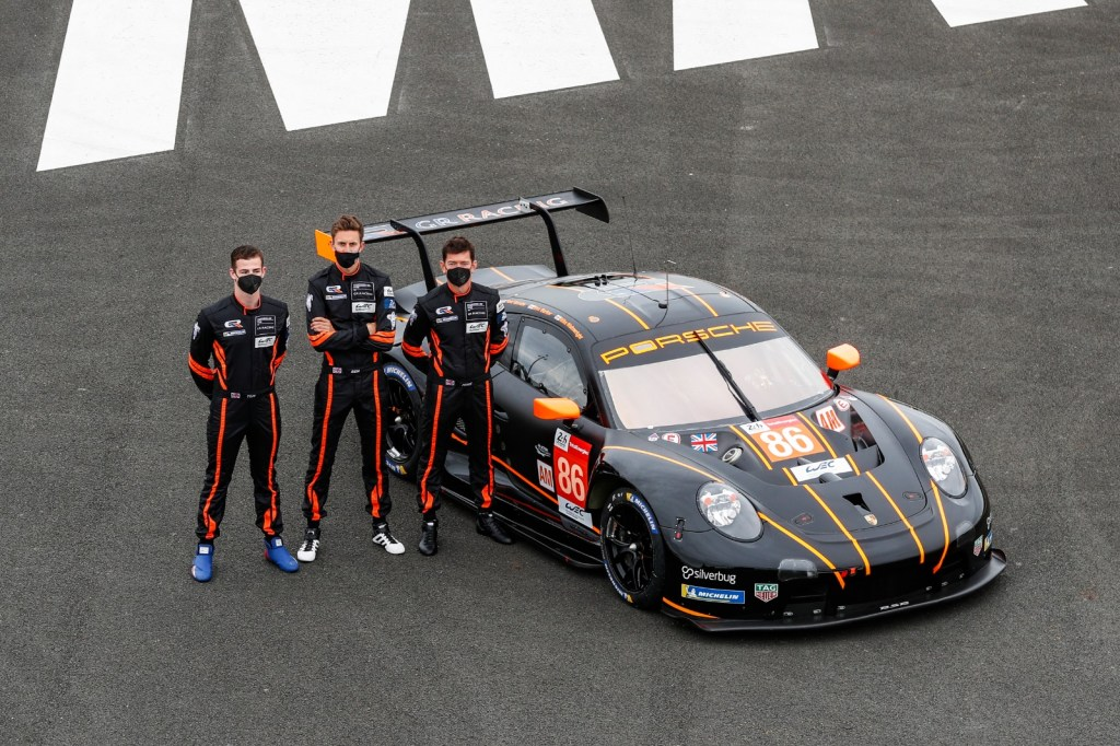 Drivers Tom Gamble, Ben Barker and Mike Wainwright stand next to the No. 86 Porsche RSR.