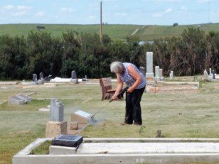 Volunteer Cleaning Headstone at Gull Lake Cemetery