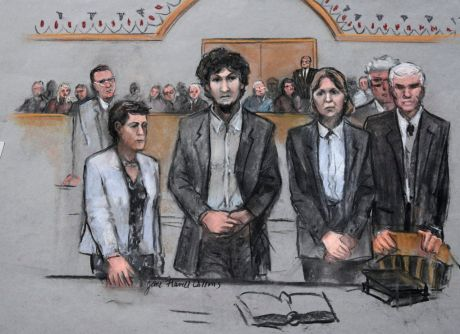 In this courtroom sketch, Boston Marathon bomber Dzhokhar Tsarnaev, center, stands with his defense attorneys as a death by lethal injection sentence is read at the Moakley Federal court house in the penalty phase of his trial in Boston, Friday, May 15, 2015. The federal jury ruled that the 21-year-old Tsarnaev should be sentenced to death for his role in the deadly 2013 attack. (Jane Flavell Collins via AP)