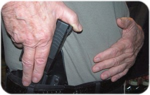 Inserting Into the Holster. Two Fingers Cover Trigger Guard As Holster Is Inserted