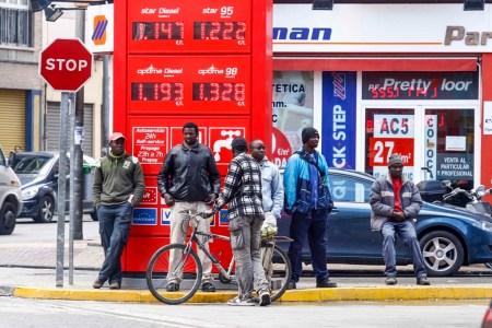 Varios subsaharianos esperan en una gasolinera para trabajar en el campo. Foto: Marcial Guillén