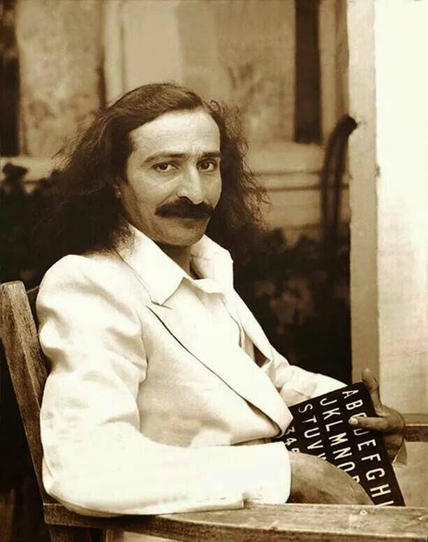 """Meher Baba was in influential spiritual master of the 20th century, who called himself the Avatar, the incarnation of God. Despite the fact that he kept silence throughout his whole life as a teacher, he lived an active life, travelled extensively and was enthusiastically received in the West as well as in India. Among all the spiritual teachers of the century, he was the one who gave the most detailed and profound explanation of the purpose of creation, the ways of spiritual evolution and the growth of the soul towards the ultimate consciousness. Meher Baba was born in zoroastrian family in India, his parents were coming from Iran. Till the age of 19 he had no spiritual inclinations, he was interested in many other things like poetry, music and sports, and lived an active social life. During his second year in college he met an old muslim saint, she kissed him in the forehead, and suddenly he felt dazed and lost interest in all the normal activities. After that he met a few other spiritual teachers, who guided him further on the journey, one of them named Upasni Maharaj became his master. When he was 27 his master told him he is ready to go and start teaching, saying """"I made him perfect."""" The name Meher Baba, meaning """"Compassionate Father"""", was given to him by his early followers. With a group of disciples he soon settled and opened an ashram in a place he called Meherabad, that became the center of his work. In 1925 he went into silence, which continued till the end of his life. First he communicated using chalk and slate, then by pointing letters on an alphabet board and later by unique system of hand gestures. Many times he said he will start speaking, even announcing the date, but this day never came. Meher Baba said, that his silence is an integral part of his spiritual work. """"Because man has been deaf to the principles and precepts laid down by God in the past, in this present Avataric form, I observe silence."""" In the 1930s Meher Baba began a period of extens"""