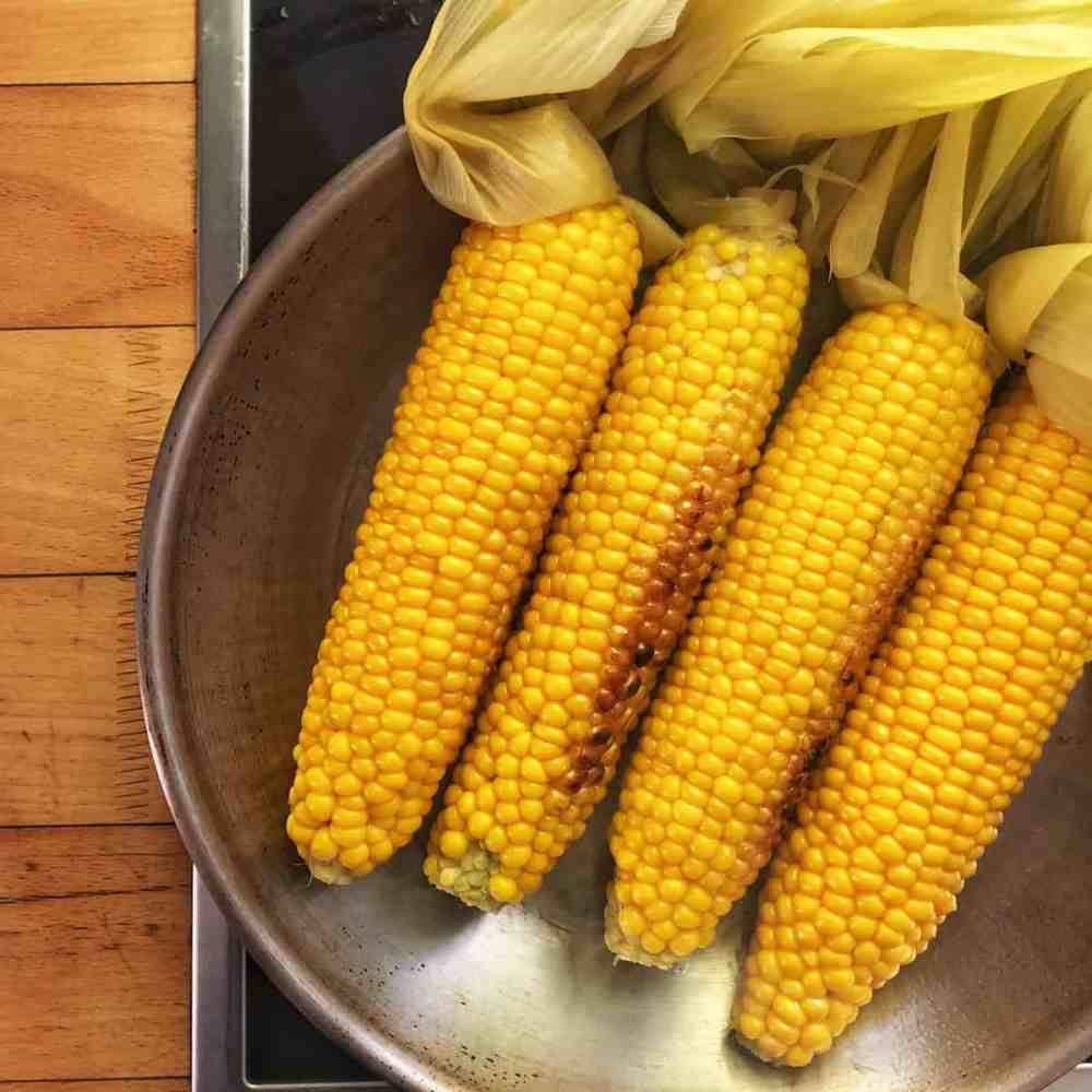 Maiskolben in die Pfanne legen und regelmäßig wenden um eine gleichmäßige Bräune zu erlangen.
