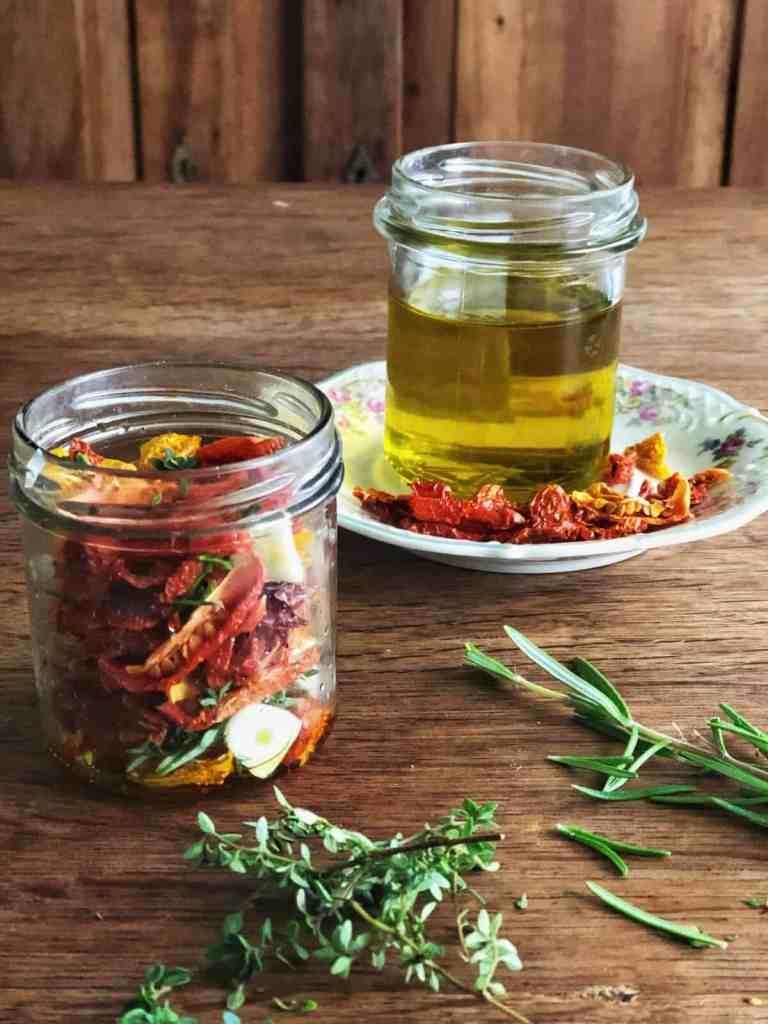 Tomaten mit Kräutern und Knoblauchscheiben in ein Schraubglas schichten.