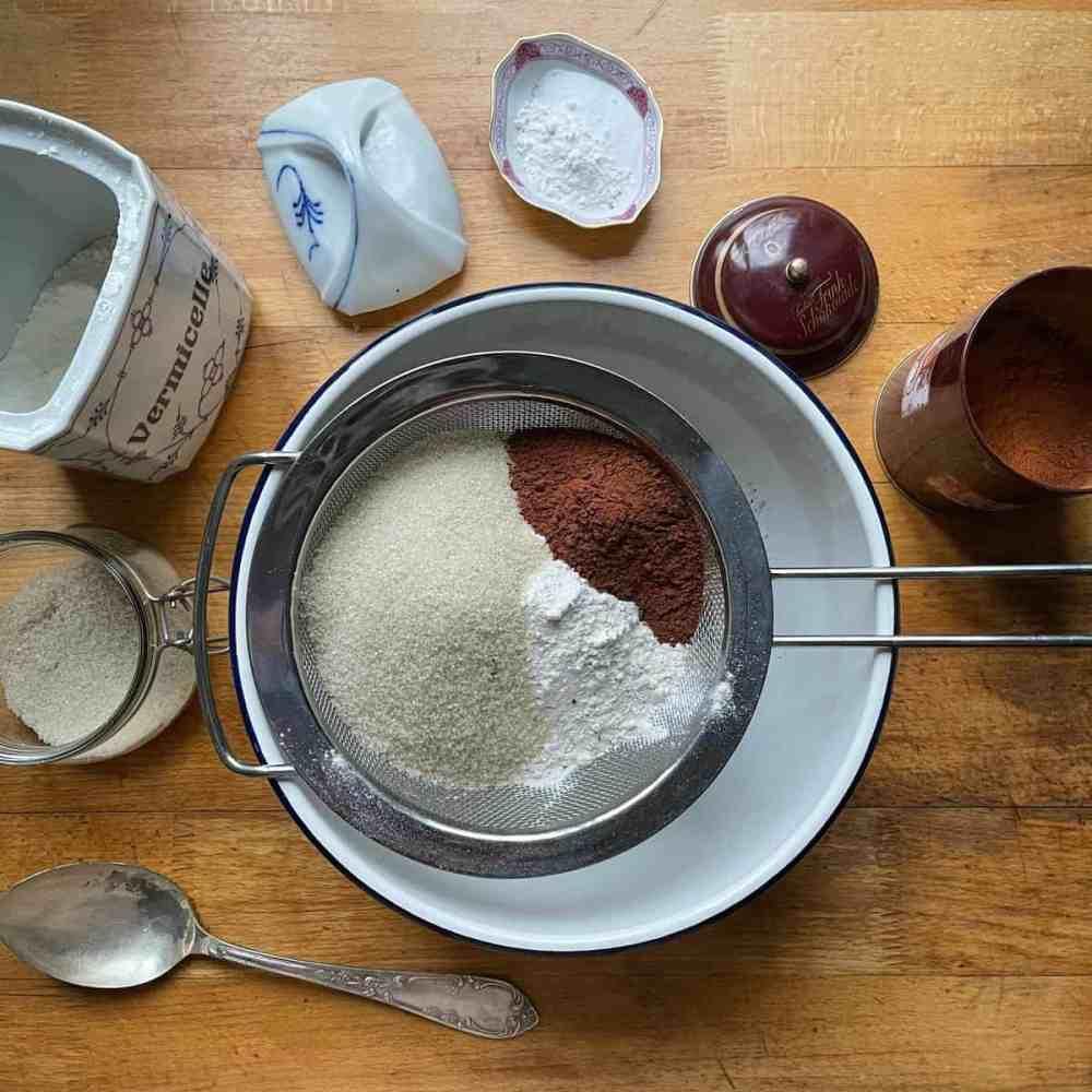 Siebe Mehl, Kakaupulver, Zucker, Backpulver und Natron in eine Schüssel.
