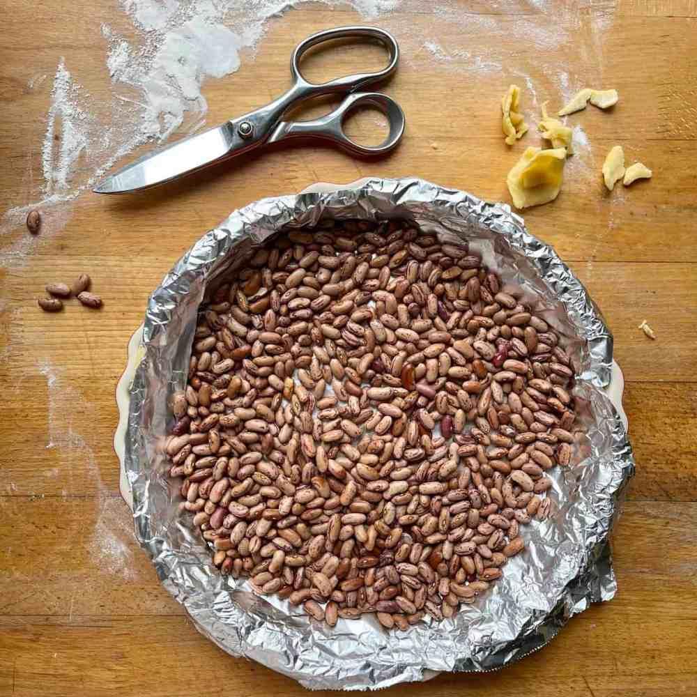 Verteile die getrocknete Bohnen oder Reis gleichmäßig auf die Alufolie.